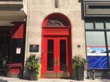 """big red front door of office with """"215"""" address and two plants on either side of the door"""